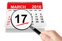 St. Patrick Day Concept. 17 march 2016 calendar with magnifier on a white background Stock Photography