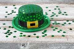 St Patrick hat and clovers in close up view. St Patrick day good luck hat with shiny clovers on rustic white wooden boards in close up view Stock Image