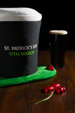 St Patrick day with a pint of black beer, hat and shamrock over Royalty Free Stock Image