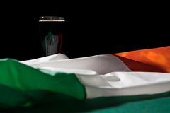 St Patrick day with a pint of black beer and irish flag over a g. Reen table and black background stock photography