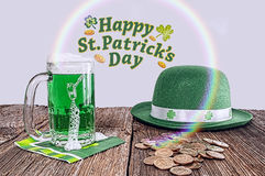 St Patrick day treasure,rainbow,hat. A St Patrick day scene with gold money, green beer,rainbow, and a green hat Stock Photos
