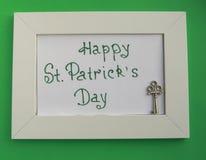 St Patrick de kaart van de daggroet met wit kader op groene achtergrond, sleutel tot rijkdom en schatten stock foto's