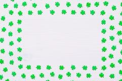 St Patrick ` s Dagachtergrond met groene quatrefoils op witte achtergrond Stock Foto's
