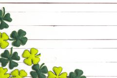 St.Patrick`s day background with felt four-leaf clover on white. Wooden table. Space for text, top view. Lucky irish shamrock stock photo