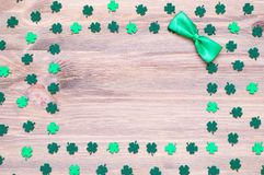 St Patrick`s Day background, free space for festive text. St Patrick`s Day festive background, green and dark green quatrefoils and bow tie on the wooden stock images