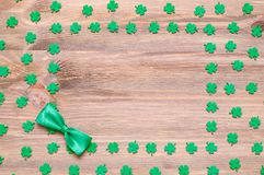 St Patrick`s Day background, free space for text. St Patrick`s Day festive background, green quatrefoils and bow tie on the wooden background with free space for stock image