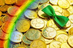 St Patrick`s Day background. Golden coins with shamrock, green bow tie and rainbow, St Patrick`s day symbols royalty free stock photos