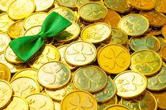 St Patrick`s Day background. Golden coins with shamrock, green bow tie, St Patrick`s day symbols royalty free stock photo