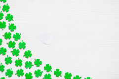 St Patrick`s Day background with green quatrefoils. St Patrick`s Day background - border of green quatrefoils on the white wooden surface royalty free stock photos