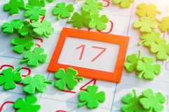 St Patrick`s Day festive background. Green quatrefoils covering the calendar with bright orange framed 17 March. St Patrick`s Day background. Green quatrefoils stock image