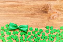 St Patrick`s Day background with green quatrefoils and green bow tie. St Patrick`s Day background - bright green quatrefoils and bow tie on the wooden background stock image
