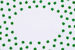 St Patrick`s Day background with green quatrefoils on white background, round border for text stock photo