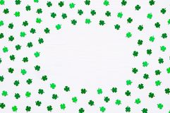 St Patrick`s Day background with green quatrefoils on white background, round border. St Patrick`s Day background. Green quatrefoils on the white wooden surface stock photography