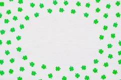St Patrick`s Day background with green quatrefoils on white background, round border. St Patrick`s Day background. Green quatrefoils, round border on the white royalty free stock photos