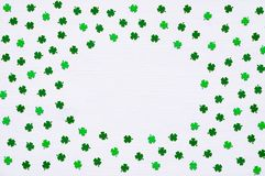 St Patrick`s Day background with green quatrefoils on white background, round border. St Patrick`s Day background. Green quatrefoils on the white wooden surface royalty free stock photos