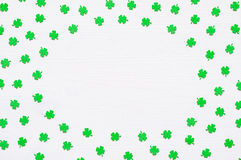 St Patrick`s Day background with green quatrefoils on white background. St Patrick`s Day background - green quatrefoils on the white wooden surface with free stock photo