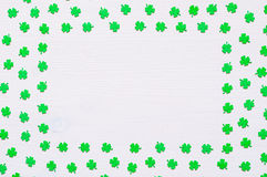 St Patrick`s Day background with green quatrefoils on white background. St Patrick`s Day background - green quatrefoils on the white wooden surface with free stock photos