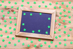 St Patrick`s Day background with green quatrefoils on the wooden background. St Patrick`s Day background - wooden frame with free space for text and green stock photo