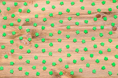 St Patrick`s Day background with green quatrefoils on the wooden background. St Patrick`s Day background - green quatrefoils on the natural wooden texture royalty free stock image
