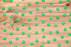 St Patrick`s Day background with green quatrefoils on the wooden background. St Patrick`s Day background - green quatrefoils on the natural wooden texture stock photos