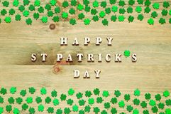 St Patricks Day background. Green quatrefoils on the wooden background and inscription Happy St Patrick`s day. St Patrick`s Day background. Green quatrefoils on Stock Photography