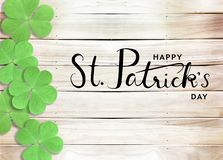 Happy St. Patrick`s Day Black Text Typography Wooden Background with Green Shamrocks clover leaf. Black Happy St. Patrick`s Day Text Typography calligraphy royalty free stock image