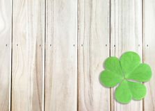 St. Patrick`s Day Background with Green Shamrocks on Wooden Texture. One Green Shamrocks at bottom right Corner on Wooden Texture Can use as St. Patrick`s Day stock image