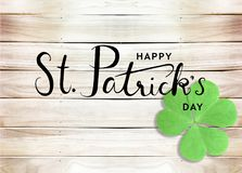 Happy St. Patrick`s Day Black Text Typography Background with Green Shamrocks on Wooden Texture stock photo