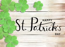 Happy St. Patrick`s Day Black Text Typography Background with Green Shamrocks on Wooden Texture stock photography