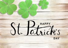 Happy St. Patrick`s Day Black Text Typography Background with Green Shamrocks on Wooden Texture royalty free stock photo