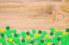 St Patrick`s Day background with one side border of green quatrefoils. On the wooden background royalty free stock photo