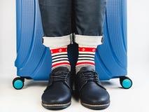 Stylish suitcase, men's legs and bright socks stock image