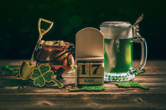 St Patrick`s Day. Block calendar for St Patrick`s Day, March 17, with green beer and pot of gold, on wooden background Royalty Free Stock Photography