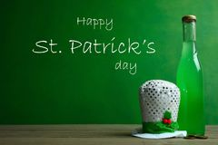 St.Patrick `s Day. A bottle of green beer and a hat on a black background. Concept day of St. Patrick Stock Photos