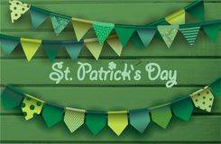 St. patrick`s day card.  Colorful paper garlands on green wooden background. Royalty Free Stock Photo