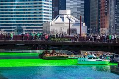 St. Patrick`s Day celebration in Chicago, with crowds gathering around a dyed green Chicago River royalty free stock image