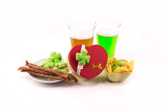 St.Patrick `s Day Celebration gift in the shape of heart two glasses of beer lager green with appetizers sausages chips and clover Royalty Free Stock Photo