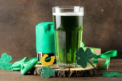 St.Patrick `s Day. celebration. green beer, leprechaun hat, coins, bow tie and clover on a brown background stock image