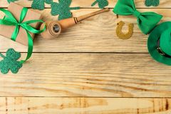 St.Patrick `s Day. celebration. Green leprechaun hat, bow tie, smoking pipe and gift box on a natural wooden background. view fro. M above. space for text royalty free stock images