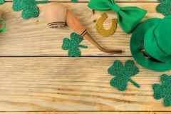 St.Patrick `s Day. celebration. Green leprechaun hat, bow tie, smoking pipe and gift box on a natural wooden background. view fro. M above. space for text stock photo