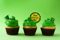 St. Patrick`s Day cupcakes. On green background stock photography