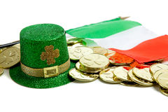 St. Patrick's day decorations on white. St. Patrick's day decorations including gold coins, green glittery leprecaun hat and irish flag on a white background Stock Photos