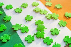 St Patrick`s Day festive background. Bright green quatrefoils above the Irish national flag stock image