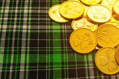 St Patrick`s Day festive background. Golden coins with shamrock on the green checkered texture cloth under soft sunshine stock photography