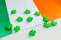St Patrick`s Day festive background. Green quatrefoils above the Irish national flag, festive card royalty free stock image