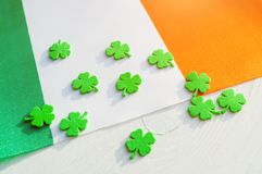 St Patrick`s Day festive background. Green quatrefoils above the Irish national flag royalty free stock photo