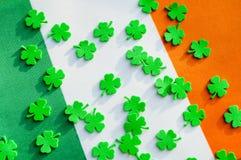 St Patrick`s Day festive background. Green quatrefoils above the Irish national flag. St Patrick`s Day holiday background. Green quatrefoils above the Irish stock image