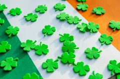 St Patrick`s Day festive background. Green quatrefoils above the Irish national flag,St Patrick`s day still life stock image