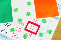 St Patrick`s Day festive background. Green quatrefoils and Irish national flag on the calendar with framed 17 March royalty free stock images