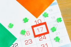 St Patrick`s Day festive background. Irish flag covering the calendar with framed 17 March, St Patrick`s day still life royalty free stock photo
